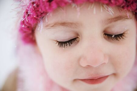Young girl with snowflakes on long dark eyelashes wearing a hat outdoors in winter. Stock Photo