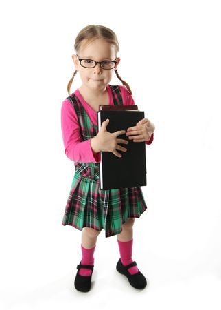Cute preschool age girl wearing eyeglasses carrying a stack of heavy books Stock Photo - 8116160