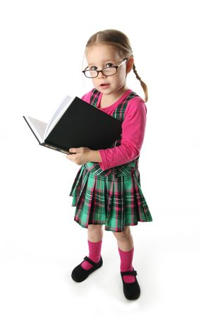 Cute preschool age girl wearing eyeglasses carrying a stack of heavy books photo