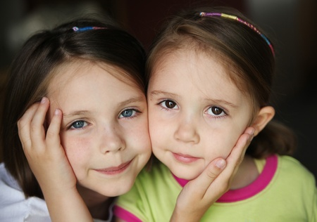 Close up of cute young sisters holding each others faces in their hands. One with blue eyes and freckles, the other with brown eyes. Stock Photo - 8383207