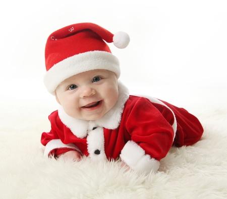 Gelukkig lachend baby liggend op de buik het dragen van een rode en witte Kerst mis Kerst muts en pak, geïsoleerd op een witte achtergrond.