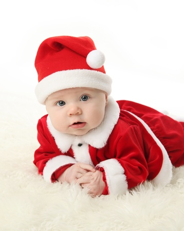 Baby lying on tummy wearing a red and white Christmas Santa hat and suit, isolated on a white background. photo