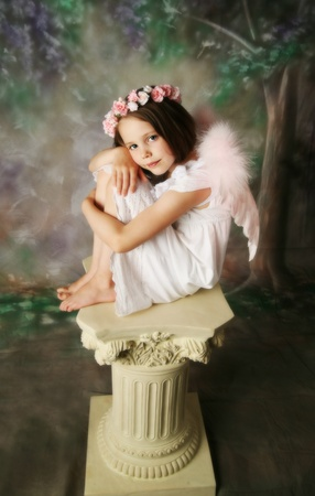 Beautiful young girl wearing pink angel wings and flower halo sitting on a pedestal