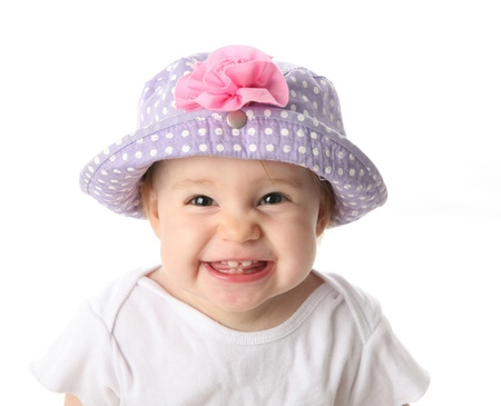 Smiling baby girl showing teeth wearing a purple polka dot hat with pink flower isolated on white background Stock Photo