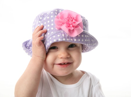 Smiling baby girl showing teeth wearing a purple polka dot hat with pink flower isolated on white background Stock Photo - 8383239