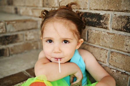 Portrait of a young girl sitting on brick steps eating a lollipop, wearing rainbow tights and a bright green tutu