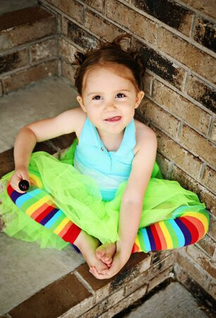Portrait of a young girl sitting on brick steps eating a lollipop, wearing rainbow tights and a bright green tutu photo