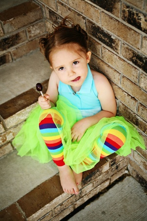 Portrait of a young girl sitting on brick steps eating a lollipop, wearing rainbow tights and a bright green tutu Stock Photo - 8383263