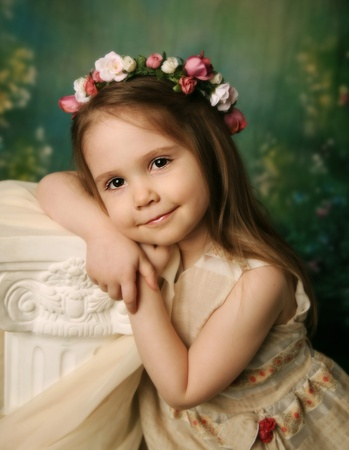 Beautiful child wearing a flower wreath halo leaning on a cream pedestal, with a serene expression on her face photo