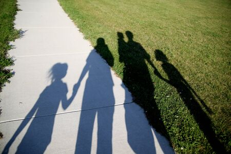 four hands: Shadows of a family of five walking in the park holding hands