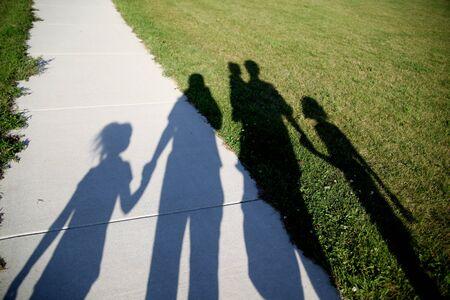 familia de cinco: Sombras de una familia de cinco caminando en el Parque de mano