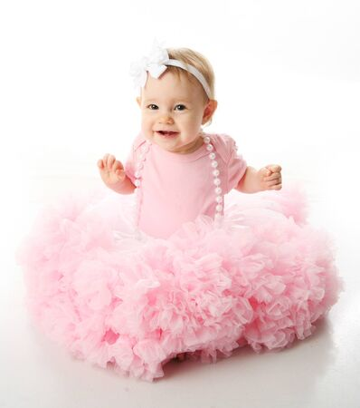 Portrait of a sweet infant wearing a pink tutu, necklace, and headband bow, isolated on white in studio Stock Photo - 8383220