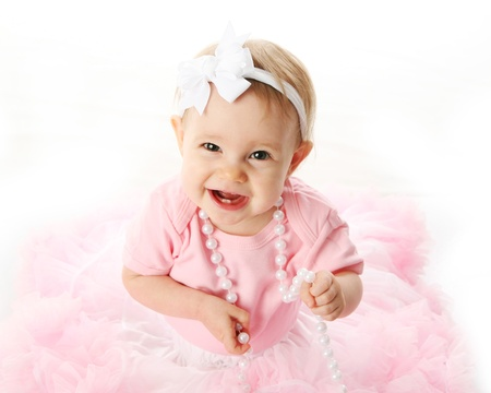 Portrait of a sweet infant wearing a pink tutu, necklace, and headband bow, isolated on white in studio photo