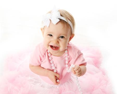 ピンクのチュチュ、ネックレス、およびヘッドバンド弓、スタジオで白で隔離される身に着けている甘い幼児の肖像画