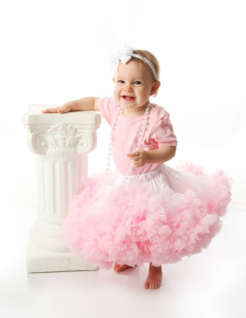 tutu: Portrait of a sweet infant wearing a pink tutu, necklace, and headband bow, isolated on white in studio