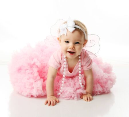 Portrait of a sweet infant wearing a pink tutu, necklace, and headband bow, isolated on white in studio