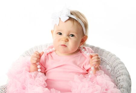 Portrait of a sweet infant wearing a pink tutu, necklace, and headband bow, isolated on white in studio with a funny expression on her face, scrunching up nose photo