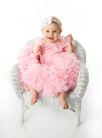 Portrait of a sweet infant wearing a pink tutu, necklace, and headband bow, isolated on white in studio sitting in a wicker childs chair  photo