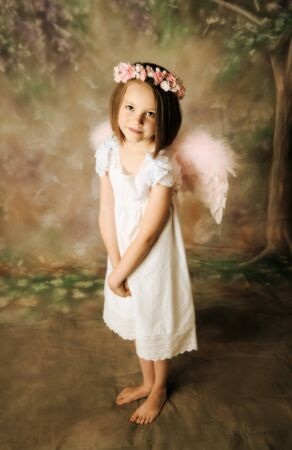 baby girls smiley face: Beautiful young girl wearing angel wings and floral halo Stock Photo