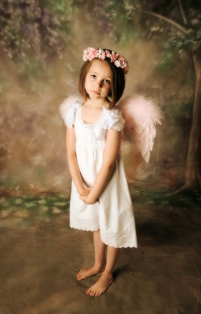 somber: Beautiful young girl wearing angel wings and flower halo with somber expression