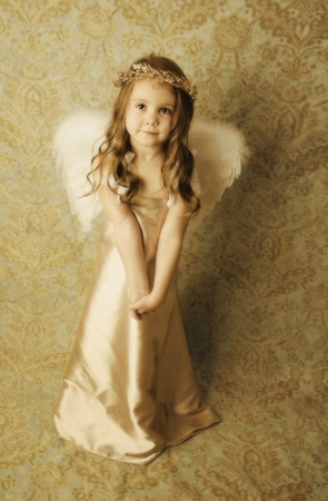 Beautiful young girl wearing angel wings and gold halo wreath with soft sweet smile expression, vintage look