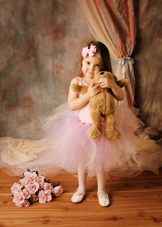 Adorable little girl dressed as a ballerina in a tutu, hugging a teddy bear standing next to pink roses.