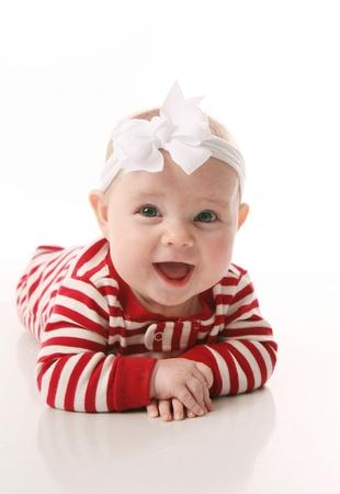 Cute baby wearing Christmas pajamas lying on tummy, isolated on white