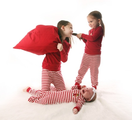 pulling faces: Three sisters dressed in Christmas pajamas. Two older girls are pulling hair and having a pillow fight while the baby is crying.