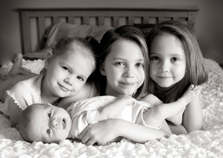 snuggling: Four little girl sisters lying on a bed snuggling Stock Photo