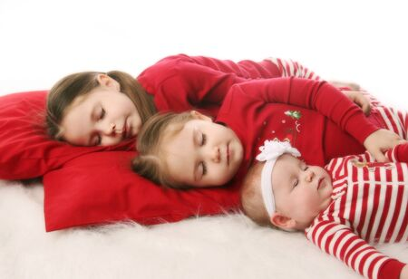 Three sisters sleeping snuggled together, dressed in Christmas pajamas