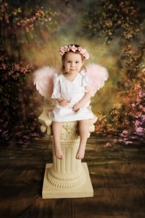 Beautiful young toddler girl wearing a white dress and pink angel wings sitting atop a vintage pedestal column Foto de archivo