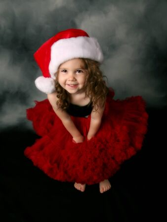 美しい若い女性子供のサンタの帽子と赤のチュチュ スカートをはいています。