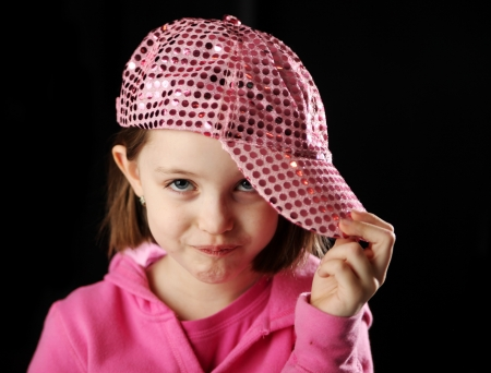 Young girl wearing a pink sequin baseball cap rolling her eyes with attitude, on black background Banque d'images