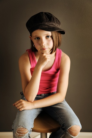 newsboy cap: Beautiful young female child wearing a newsboy cap and ripped jeans