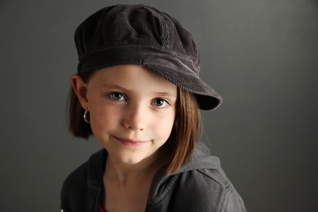 신문 보이 모자와 후프 귀걸이를 쓰고 아름 다운 젊은 여성 자식의 폐쇄