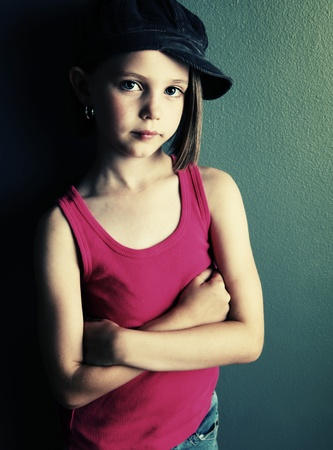Beautiful young female child wearing a newsboy cap and ripped jeans, gray background in studio 写真素材