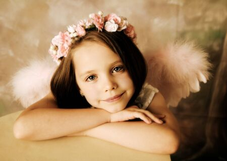 Beautiful young girl wearing angel wings and floral halo Stock Photo