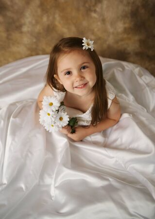 Beautiful young female child wearing her mothers wedding dress which is too big for her photo