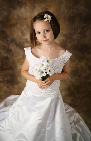 Beautiful young female child wearing her mother's wedding dress which is too big for her Stock Photo - 8476261