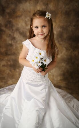 Beautiful young female child wearing her mother's wedding dress which is too big for her Stock Photo - 8476240