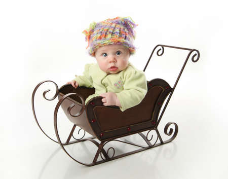 Adorable young baby girl wearing a knit stocking cap sitting in a metal Christmas snow sleigh Stock Photo
