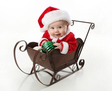 sledge: Adorable beb� joven vistiendo un traje de santa claus y sombrero, sentado en un trineo de nieve de Navidad metal sosteniendo un ornamento