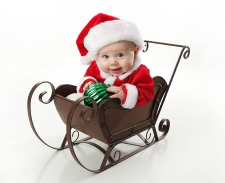 Adorable young baby wearing a santa claus suit and hat sitting in a metal Christmas snow sleigh holding an ornament