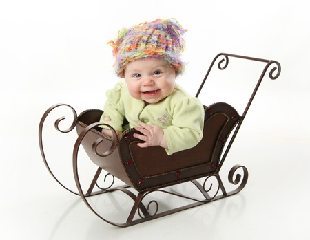 Adorable young baby girl wearing a knit stocking cap sitting in a metal Christmas snow sleigh   photo