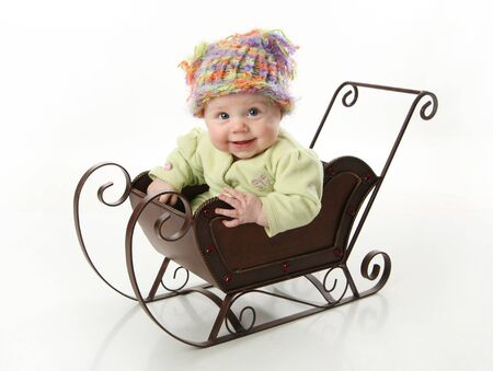 stocking cap: Adorable young baby girl wearing a knit stocking cap sitting in a metal Christmas snow sleigh