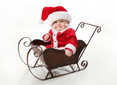 baby christmas: Adorable young baby wearing a santa claus suit and hat sitting in a metal Christmas snow sleigh