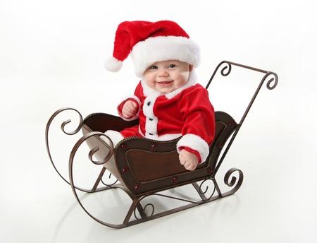 sledge: Adorable beb� joven vistiendo un traje de santa claus y sombrero, sentado en un trineo de nieve de Navidad metal   Foto de archivo