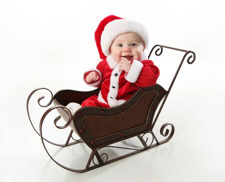Adorable young baby wearing a santa claus suit and hat sitting in a metal Christmas snow sleigh    Stock Photo