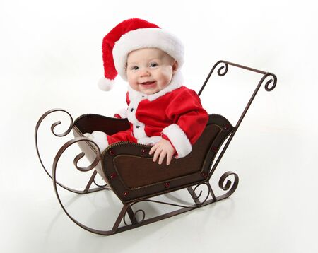 Adorable young baby wearing a santa claus suit and hat sitting in a metal Christmas snow sleigh  版權商用圖片