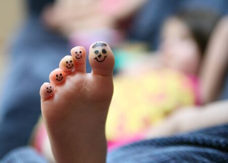Bored little lying on couch girl showing the bottom of her foot with smiley faces drawn on her toes